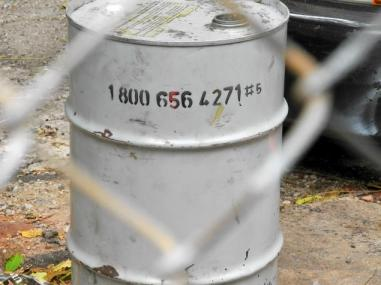 Photo by Beth Stebner via New York Daily News: 1-800 number on a barrel at Banksy's monochrome war/apocolypse installation leads to audio from a 2007 covert operation released in 2010 by WikiLeaks.